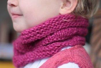 Jeune enfant avec une écharpe snood rose en laine